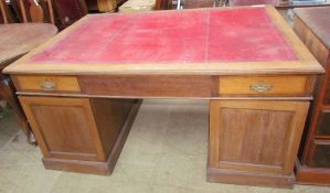 An early 20th century oak partners desk with a leather inset top,