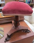 A Victorian rosewood piano stool with a square pad upholstered seat on a leaf carved columns and