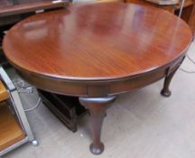 An Edwardian mahogany extending dining table of oval form with cabriole legs and pad feet,