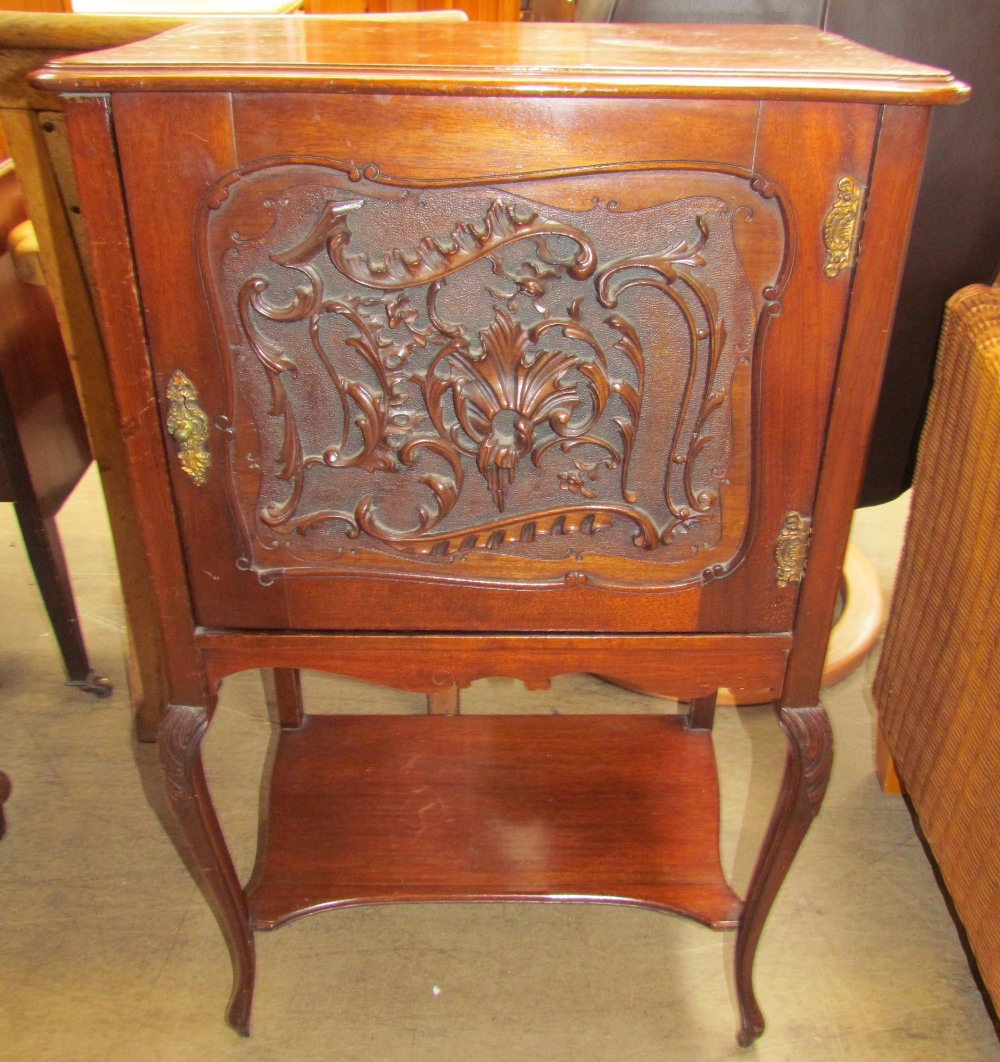 Lot 22 - An Edwardian mahogany music cabinet with a leaf carved door on leaf carved cabriole legs united by