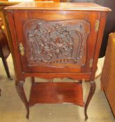 An Edwardian mahogany music cabinet with a leaf carved door on leaf carved cabriole legs united by
