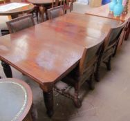 An Edwardian walnut extending dining table on tapering legs,