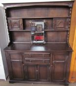 A 20th century oak dresser with a shelved and cupboard top, the base with drawers and cupboards