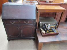 A reproduction mahogany bureau together with a Singer sewing machine in a faux crocodile case and