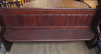 A pine pew, with a panelled back and a solid seat on stiles