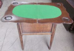 An oak games table, with a foldover top, oval baize interior and counter well, containing bone