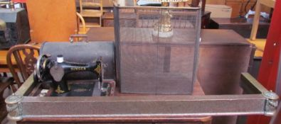 An electroplated fire fender together with a brass fire guard and a Singer sewing machine