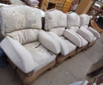A set of four conservatory armchairs with floral upholstery and another wicker armchair
