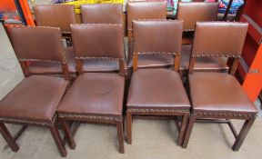 A set of eight oak dining chairs with brown leatherette coverings