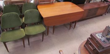 A mid 20th century teak extending dining table together with a set of four upholstered dining chairs