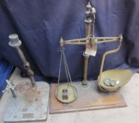 A brass balance scales with some weights together with a Dental press base