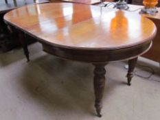 An Edwardian oak extending dining table with two additional leaves on reeded and fluted legs and
