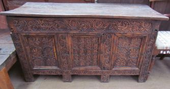 A 17th century carved coffer with a planked top and carved front