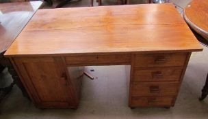 A 20th century walnut desk with a rectangular top above a central drawer, with a cupboard to one
