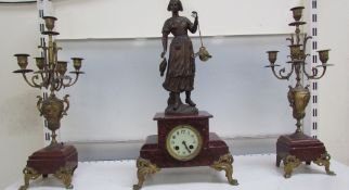 A clock garniture with a fisherwoman surmount, flanked by a pair of candelabra