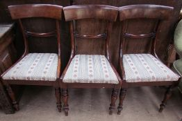 A set of three Regency mahogany dining chairs with an outswept top rail with a bar back and drop