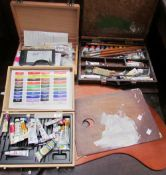 Artists pallets together with paints, brushes etc