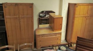 A 20th century oak bedroom suite comprising two wardrobes, dressing table and bedside cabinet