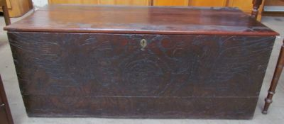 A 17th century hardwood coffer, with a planked top above a chip carved front depicting eagles and