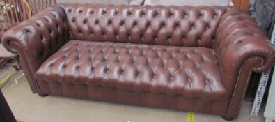A brown leather three seater chesterfield settee