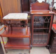 An Edwardian mahogany cabinet with a carved cornice above a glazed door with glazing bars,