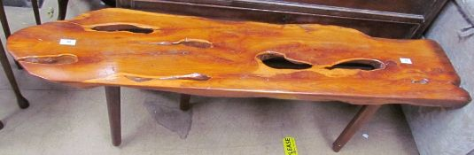 A yew coffee table of irregular shape on four tapering legs