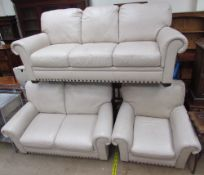A cream leather three piece suite comprising a three seater settee,