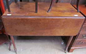 A Victorian mahogany Pembroke table with drop flaps and a drawer on ring turned legs and casters