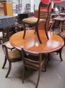 A reproduction mahogany extending dining table together with an additional leaf and five Regency