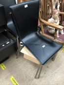 A set of four black leatherette dining chairs on chrome legs