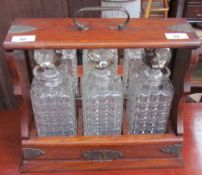 An oak tantalus with electroplated mounts and three glass decanters