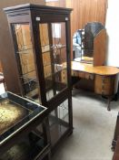 A 20th century oak display cabinet with a pair of leaded glazed doors and glazed sides