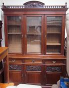 An Edwardian mahogany bookcase, with a carved spindle cornice above three glazed doors,