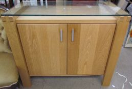 A modern oak side cabinet with a glass top and two doors on square legs