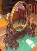 A Victorian style toilet mirror with an oval plate supported between carved uprights