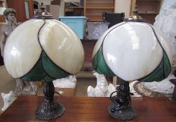 A pair of Tiffany style table lamps with marbled cream and green glass shades on naturalistic bases