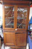A George III oak and mahogany standing corner cupboard with a moulded cornice above a pair of