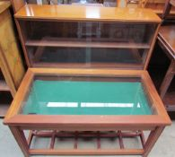 A teak bijouterie table with a hinged glazed top on square legs together with a teak bookcase with