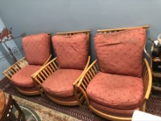 A set of three light elm Ercol elbow chairs with pad upholstered seats and back