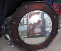 A pair of oak framed wall mirrors of octagonal form together with another mirror