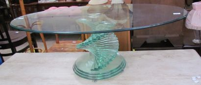 A modern glass coffee table of oval form on a stepped scrolling glass column and stepped circular