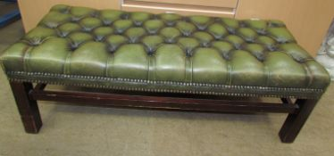 A green leather foot stool with a button upholstered top on square legs