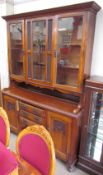 An Edwardian oak kitchen dresser with a moulded cornice above a pair of glazed doors and a leaded