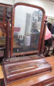 A 19th century mahogany toilet mirror, the rectangular plate with a rounded top,