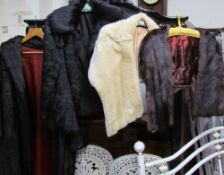 A faux fur coat together with a black fur jacket and two fur stoles