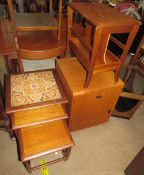 A mid 20th century teak nest of tables with a tiled top,