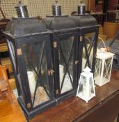 A set of three black painted storm lanterns together with a pair of cream storm lanterns and