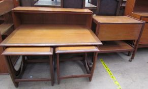 A teak nest of three tables comprising a coffee table and two side tables,