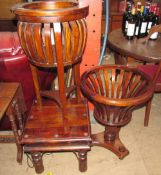 A modern mahogany plant stand with slatted sides on three legs,