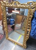 A large gilt wall mirror with scrolling leaf and flower decoration and a bevelled plate together
